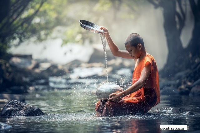 Buddhist Monk, sitting by a river.  Pouring a water from a height and sitting in contemplation.